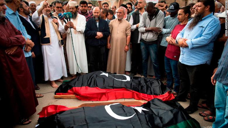 Libyans pray by the bodies of fighters loyal to the Government of National Accord during their funeral in Tripoli on April 24.