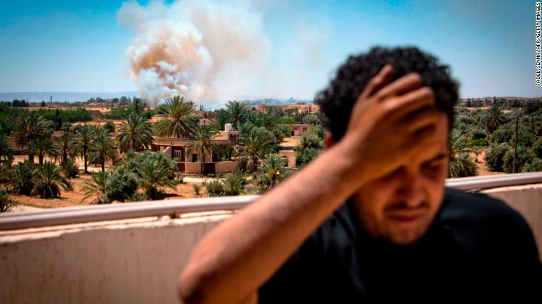 A fighter loyal to the internationally recognized Government of National Accord stands on a rooftop as smoke rises in the distance during clashes with forces loyal to Haftar in Espiaa, about 40 kilometers (25 miles) south of Tripoli, on April 29.