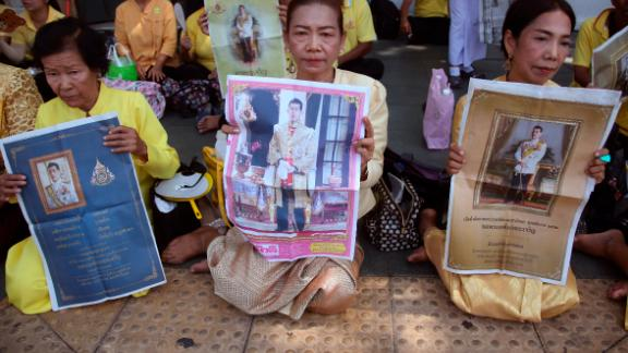 Thai well-wishers hold portraits of Thailand's King Maha Vajiralongkorn outside the Grand Palace on May 5.