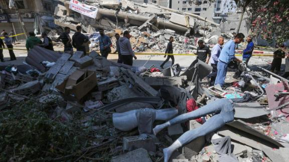 Palestinians walk by a clothing shop damaged by Israeli airstrikes on Saturday.