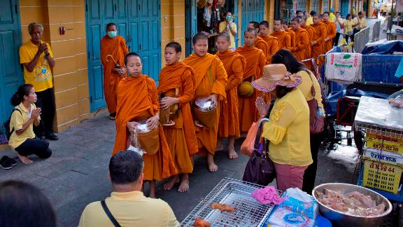 Thai people make offerings to Buddhist monks near the Grand Palace on May 5.