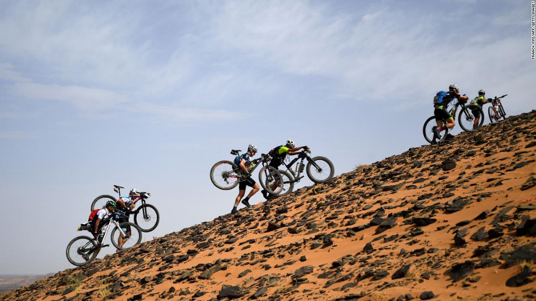Competitors carry their bicycles along a sand dune during Stage 2 of the 14th edition of Titan Desert 2019 mountain biking race between Merzouga and Ouzina in Morocco on Monday, April 29.