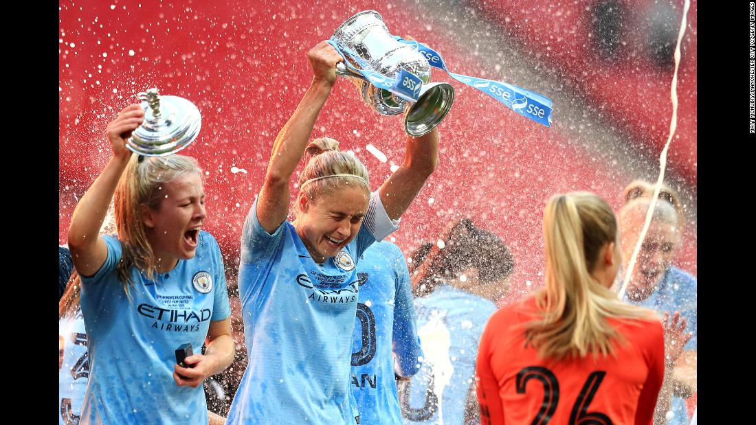 Lauren Hemp, left, and Steph Houghton, center, of the Manchester City Women celebrate with their teammates after winning the Women's FA Cup Final against the West Ham United Ladies at Wembley Stadium on May 4 in London, England.
