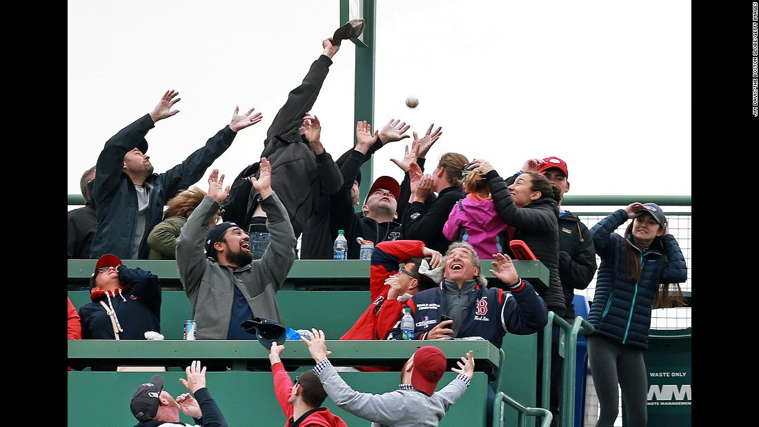 Fans seated in the Green Monster seats attempt to catch a home run ball hit by Red Sox player Christian Vazquez during the bottom of the eighth inning of a game against the Oakland Athletics at Fenway Park on May 1 in Boston.