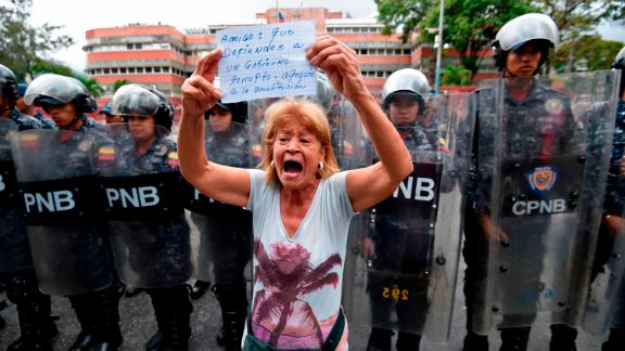 A woman demonstrates in front of police outside the Venezuelan navy headquarters in Caracas on Saturday, May 4.
