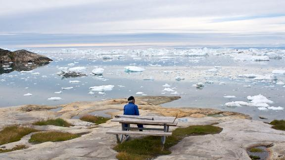 Old man enjoying the view over Ilulissat ice fjord and the Disko bay, West Greenland.