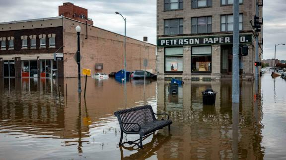 Floodwaters surround a bench near the main breach in the Mississippi River in Davenport, Iowa, on Friday, May 3, 2019.