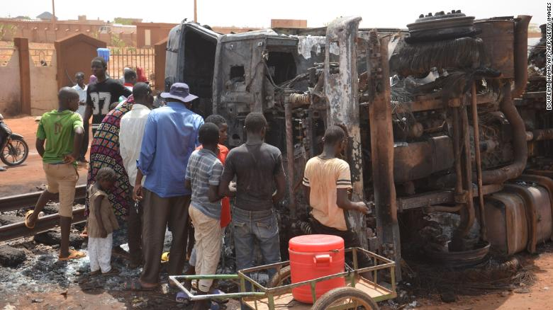 Residents look at a charred tanker truck after an explosion killed more than 55 people near the airport of Niamey.