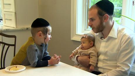 Shimon Singer with his two-month-old daughter, Malky, and son, Dovi.