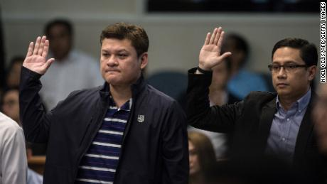 Davao City Vice Mayor Paolo Duterte, son of Philippine President Rodrigo Duterte, and the president's son-in-law, Manases Carpio, take an oath as they attend a senate hearing in Manila on September 7, 2017.