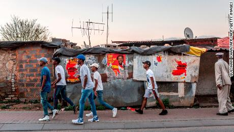 People walk past posters for the South African opposition political party, Economic Freedom Fighters (EFF) in the run up to elections on April 28, 2019 in Johannesburg. - Elections due to take place on May 8, will mark the 25th anniversary of democratic rule in the country. (Photo by GULSHAN KHAN / AFP)        (Photo credit should read GULSHAN KHAN/AFP/Getty Images)