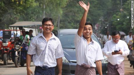 Reuters journalists Kyaw Soe Oo (right) waves beside colleague Wa Lone as they walk out of Insein prison after being freed in a presidential amnesty in Yangon on May 7, 2019. AFP/Getty Images