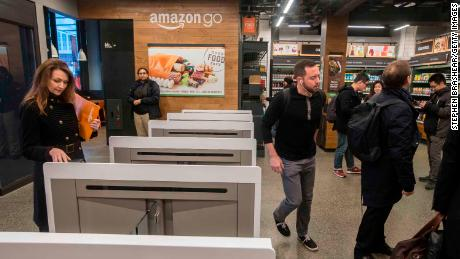 Shoppers scan the Amazon Go app on the mobile devices as the enter the Amazon Go store in Seattle, Washington.