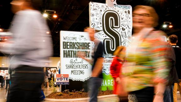 People walk past signs welcoming them to the annual Berkshire Hathaway shareholders meeting in Omaha, Neb., Friday, May 3, 2019. On Saturday estimated 40,000 people are expected in town for the event, where Chairman and CEO Warren Buffett and Vice Chairman Charlie Munger will preside over the meeting and spend hours answering questions. (AP Photo/Nati Harnik)