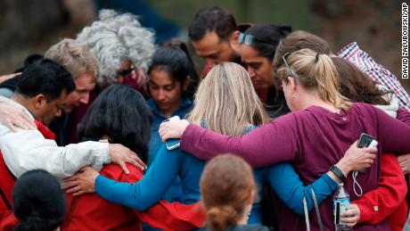 Parents gather in a circle to pray at a recreation center where students were reunited with their parents Tuesday, May 7, 2019, in Highlands Ranch, Colo. (AP Photo/David Zalubowski)
