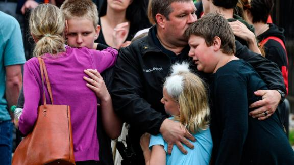 HIGHLANDS RANCH, CO - MAY 07: A police officer hugs his kids after they were evacuated to the Recreation Center at Northridge after at least seven students were injured during a shooting at STEM School Highlands Ranch on May 7, 2019 in Highlands Ranch, Colorado. (Photo by Michael Ciaglo/Getty Images)