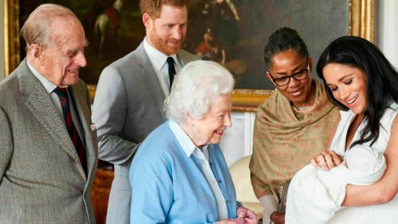 Queen Elizabeth II looks at her new great-grandchild on Wednesday. Prince Philip is on the left. Meghan's mother, Doria Ragland, is next to her at right.
