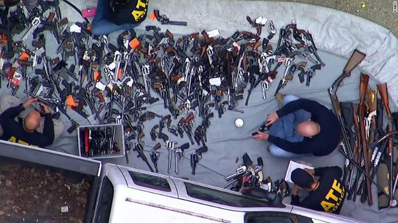 Officers take inventory of guns outside a home in the Holmby Hills section of Los Angeles.