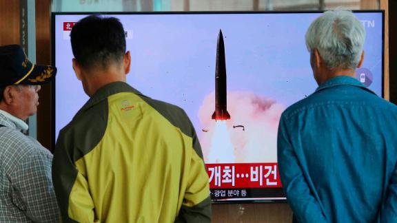 People watch a TV showing a file photo of North Korea