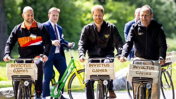 Former Dutch military sodlier and athlete Dennis van der Stroom, Britain's Prince Harry and host Lieutenant General Mart de Kruif ride bides during the presentation of The Invictus Games in The Hague.
