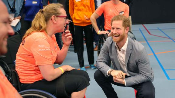 Prince Harry speaks with athletes during a sports training session at Sportcampus Zuiderpark.