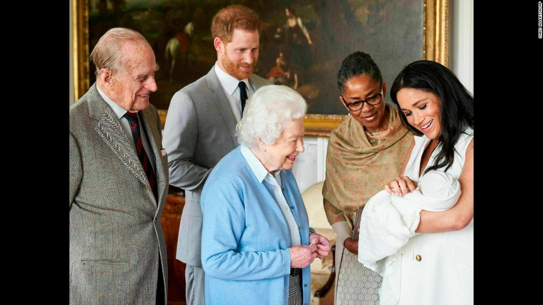 "Britain's Queen Elizabeth II looks at her new great-grandchild, Archie, on Wednesday, May 8. <a href=""http://www.cnn.com/2019/05/08/uk/gallery/archie-royal-baby-harry-meghan/index.html"" target=""_blank"">Archie</a> is the first child of Prince Harry, second from left, and his wife Meghan, the Duchess of Sussex. Prince Philip is on the far left. Meghan's mother, Doria Ragland, is next to her at right."