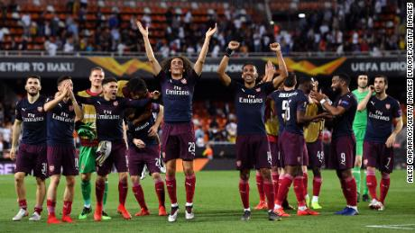 Matteo Guendouzi and Pierre-Emerick Aubameyang of Arsenal celebrate victory with their teammates.