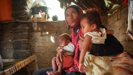 Hajja Ibrahim holds her son and her daughter inside their hut in the village of Bani Qais.