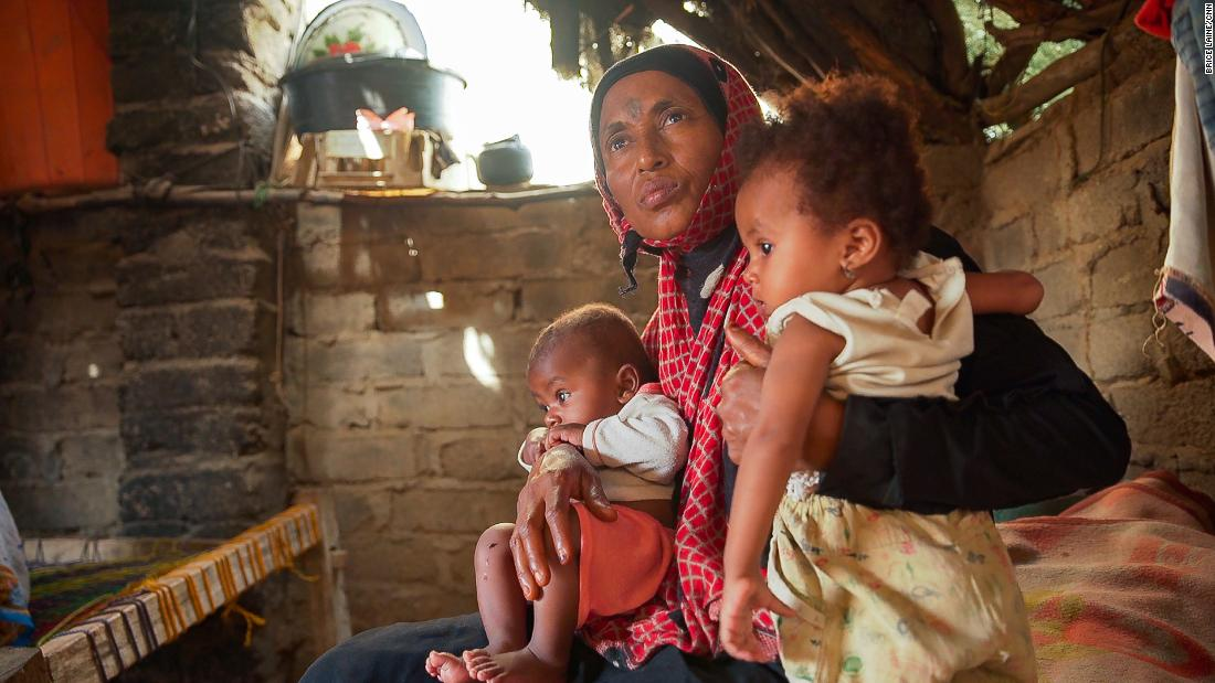 Issham Beshir sits on her mother's lap with her younger brother inside their hut in the village of Bani Qais.