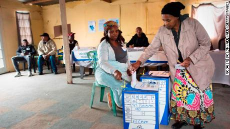 A woman casts her vote in a large shack being used as a voting station in an impoverished area in Khayelitsha on May 8, 2019 in Cape Town during South Africa's national and provincial elections. - South Africans began voting today in national elections which the ruling ANC, in power since 1994, is favourite to win despite corruption scandals, sluggish economic growth and record unemployment. The ANC has won all the past five elections, but today's vote is set to be an electoral test on whether the party has staunched a decline in popularity. (Photo by RODGER BOSCH / AFP)        (Photo credit should read RODGER BOSCH/AFP/Getty Images)