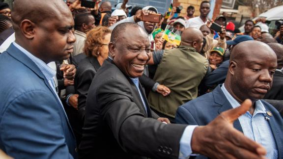 Cyril Ramaphosa greets voters as he arrives to cast his vote.