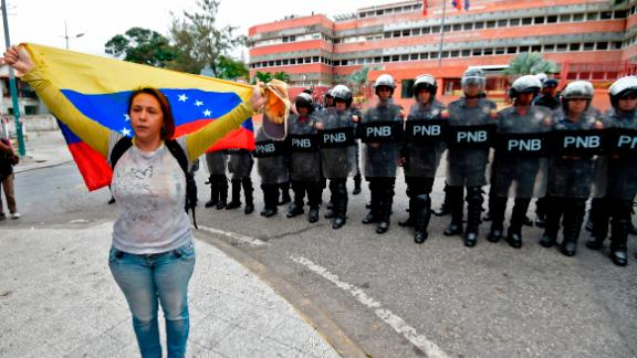 """A woman demonstrates with a Venezuelan national flag, in front of a line of riot police outside the Venezuelan Navy command headquarters at San Bernardino neighborhood in Caracas on May 4, 2019. - Venezuelan President Nicolas Maduro called on the armed forces to be """"ready"""" in the event of a US military offensive against the South American country, in a speech to troops on Saturday. His speech at a military base came as opposition leader Juan Guaido rallied his supporters in a new day of protests to press the armed forces to support his bid to dislodge Maduro. (Photo by Juan BARRETO / AFP)        (Photo credit should read JUAN BARRETO/AFP/Getty Images)"""