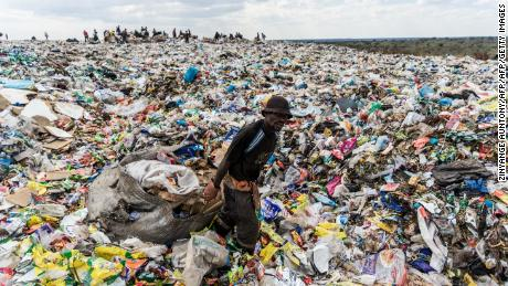 A recycler drags a huge bag of paper through a heap of non-recyclable waste in Zimbabwe.