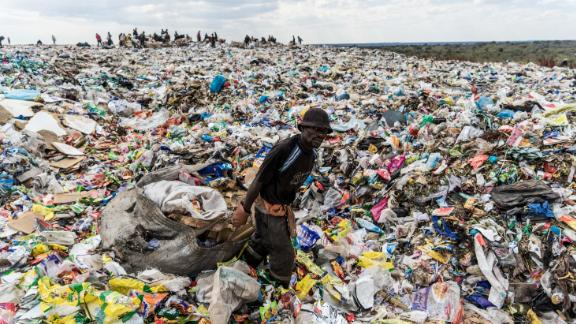 TOPSHOT - A recycler drags a huge bag of paper sorted for recycling past a heap of non-recyclable material at Richmond sanitary landfill site on 2 June 2018 in the industrial city of Bulawayo. - Plastic waste remains a challenging waste management issue due to its non-biodegrable nature, if not managed properly plastic end up as litter polluting water ways, wetlands and storm drains causing flash flooding around Zimbabwe's cities and towns. Urban and rural areas are fighting the continuous battle against a scourge of plastic litter. On June 5, 2018 the United Nations mark the World Environment Day which plastic pollution is the main theme this year. (Photo by Zinyange Auntony / AFP)        (Photo credit should read ZINYANGE AUNTONY/AFP/Getty Images)