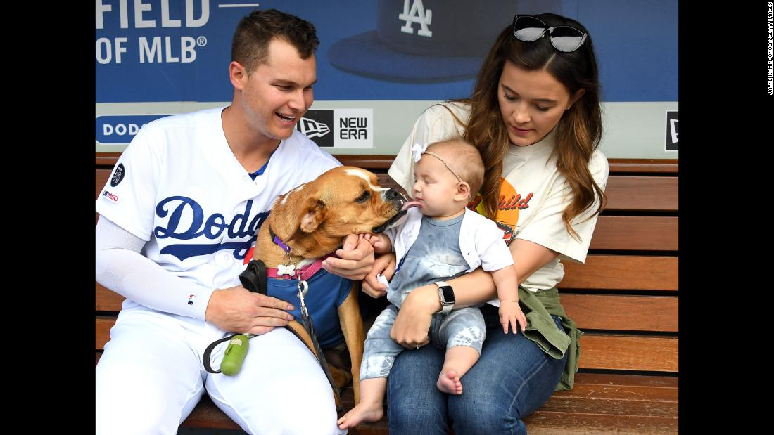 Joc Pederson of the Los Angeles Dodgers poses with his wife Kelsey, dog Blue and daughter Poppy as more than 700 dogs attend the game between the Dodgers and the Washington Nationals for the annual Pups at the Park promotion at Dodger Stadium on May 11 in Los Angeles.