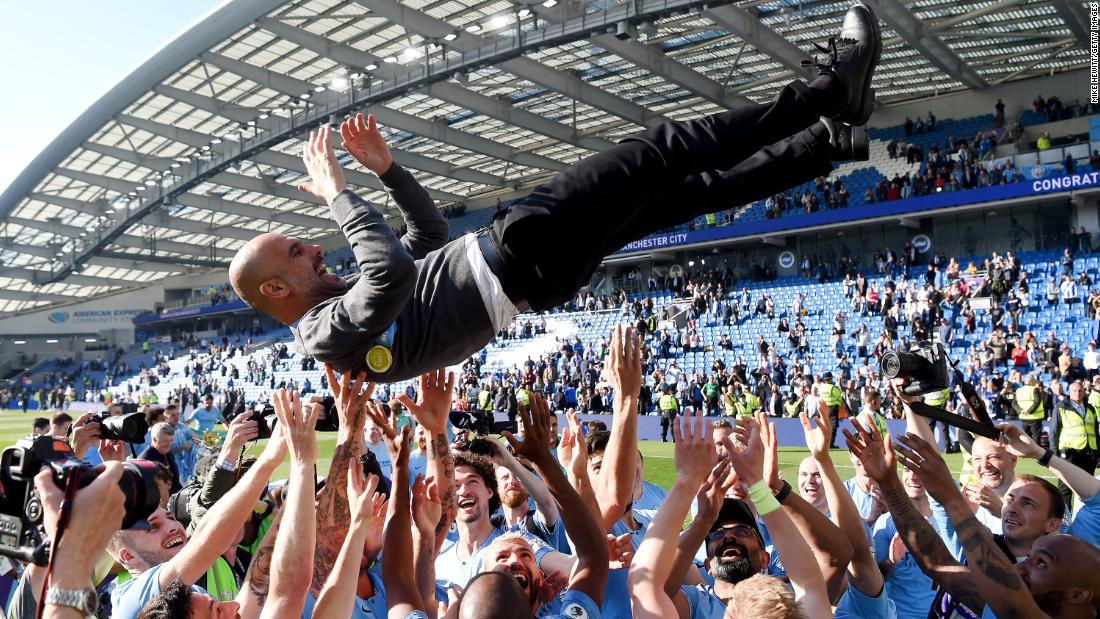 Manchester City players throw manager Josep Guardiola in the air as they celebrate winning the Premier League title following a match against Brighton & Hove Albion at American Express Community Stadium on May 12 in Brighton, England. The final score was 4-1.