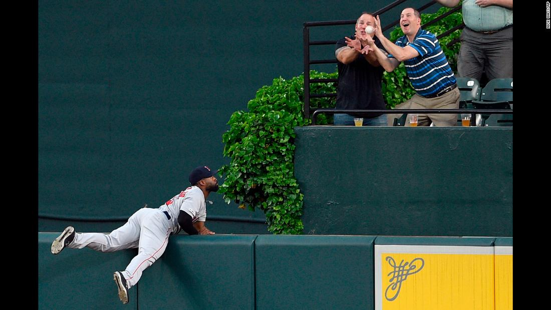 Boston Red Sox center fielder Jackie Bradley Jr. watches fans go for a ball hit by the Baltimore Orioles' Jonathan Villar for a grand slam during the second inning of a baseball game on May 6 in Baltimore.