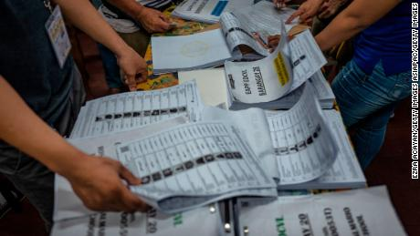 Election workers sort lists of voters at a polling precinct in Manila.