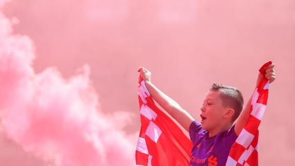 A young Liverpool fan cheers outside Anfield as flares are set off ahead of their team's final match of the season.