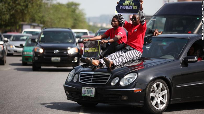 Two women display their placards as they sit on a car during one of the protest in Abuja on May 10.