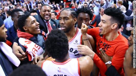 TORONTO, ON - MAY 12:  Kawhi Leonard #2 of the Toronto Raptors celebrates with teammates after sinking a buzzer beater to win Game Seven of the second round of the 2019 NBA Playoffs against the Philadelphia 76ers at Scotiabank Arena on May 12, 2019 in Toronto, Canada.  NOTE TO USER: User expressly acknowledges and agrees that, by downloading and or using this photograph, User is consenting to the terms and conditions of the Getty Images License Agreement.  (Photo by Vaughn Ridley/Getty Images)
