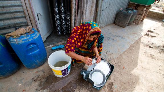 Residents of Vasant Kunj slum try to stretch water as much as possible by reusing dirty water to wash cooking utensils.