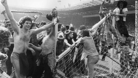 Scottish football fans invading the pitch and pulling down goalposts after Scotland's men beat England 2-1 at Wembley Stadium in 1977.