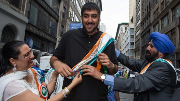 Sim Bhullar is flanked by his parents as he takes part as a marshal during the Indian Day Parade on August 17, 2014 in New York.