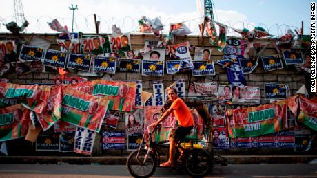 A rickshaw driver passes campaign posters in front of Baseco Elementary School in Manila on May 13, 2019. - Filipinos headed to the polls on May 13 in a vote that is expected to strengthen President Rodrigo Duterte's grip on power, opening the way for him to deliver on pledges to restore the death penalty and rewrite the constitution. (Photo by Noel CELIS / AFP)        (Photo credit should read NOEL CELIS/AFP/Getty Images)