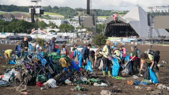 Festivals are facing mounting pressure to clean up their act, lower emissions and cut down on waste. Here are some easy ways you can enjoy a festival this summer without trashing the planet.   Pictured: Litter collectors clearing the fields in front of the main Pyramid Stage at Glastonbury Festival in the UK.