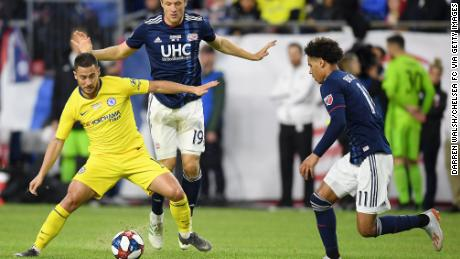 Eden Hazard of Chelsea is challenged by Antonio Mlinar Delamea and Tajon Buchanan of New England Revolution during a soccer match on Wednesday.