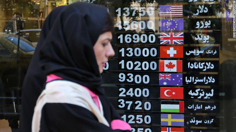 An Iranian woman walks past a currency exchange shop in the capital Tehran, Iranians, where locals are hard hit by punishing US economic sanctions