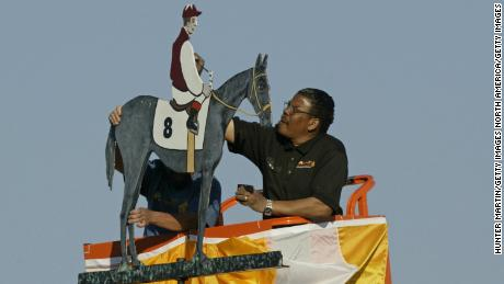 An artist paints the winning colors on the weather vane at Pimlico Race Track after the Preakness Stakes.