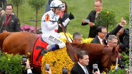 Jockey Mike Smith and racing horse Justify enter the winners circle at the 143rd Preakness Stakes.